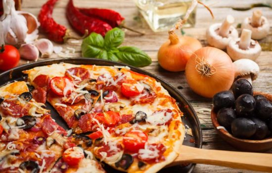 Taking slice of homemade pizza